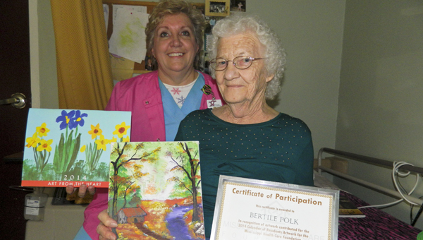 """Shirley Burnham / The Prentiss Headlight – The artwork of Bertile Polk was chosen out of over 200 entries to be """"September"""" in a calendar produced by the Mississippi Healthcare Foundation Association. Jeff Davis County ECF Activities Director Wanda Hamilton (left) displays the calendar next to Polk's artwork."""