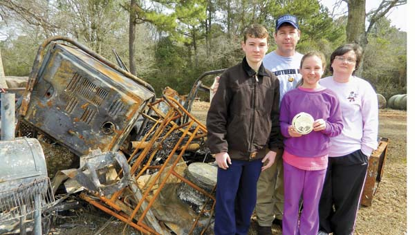 Shirley Burnham / The Prentiss Headlight—Ryan, Richard, Kristi and Hanna Lee stand in front of what is left of their home, a pile of metal for junk. Hanna holds a smoke detector like one that most likely saved their lives.