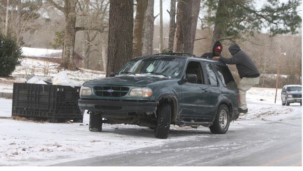 Karen Sanford / The Prentiss Headlight — The hill on Granby Road and old Highway 84 was an icy trap for motorist during the winter storm on Wednesday. Above, men jump on the back bumper of an SUV to help gain traction on the slippery road.