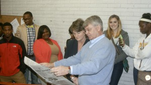 Prentiss Headlight President and Publisher Karen Sanford / The Prentiss Headlight—Otis Raybon holds out a paper hot off the press for BHS journalism teacher Melissa Martin to see.